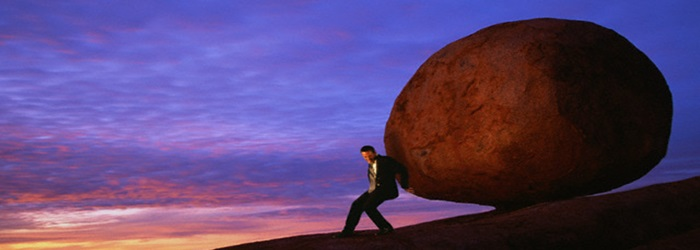 Businessman Pushing Boulder up Hill